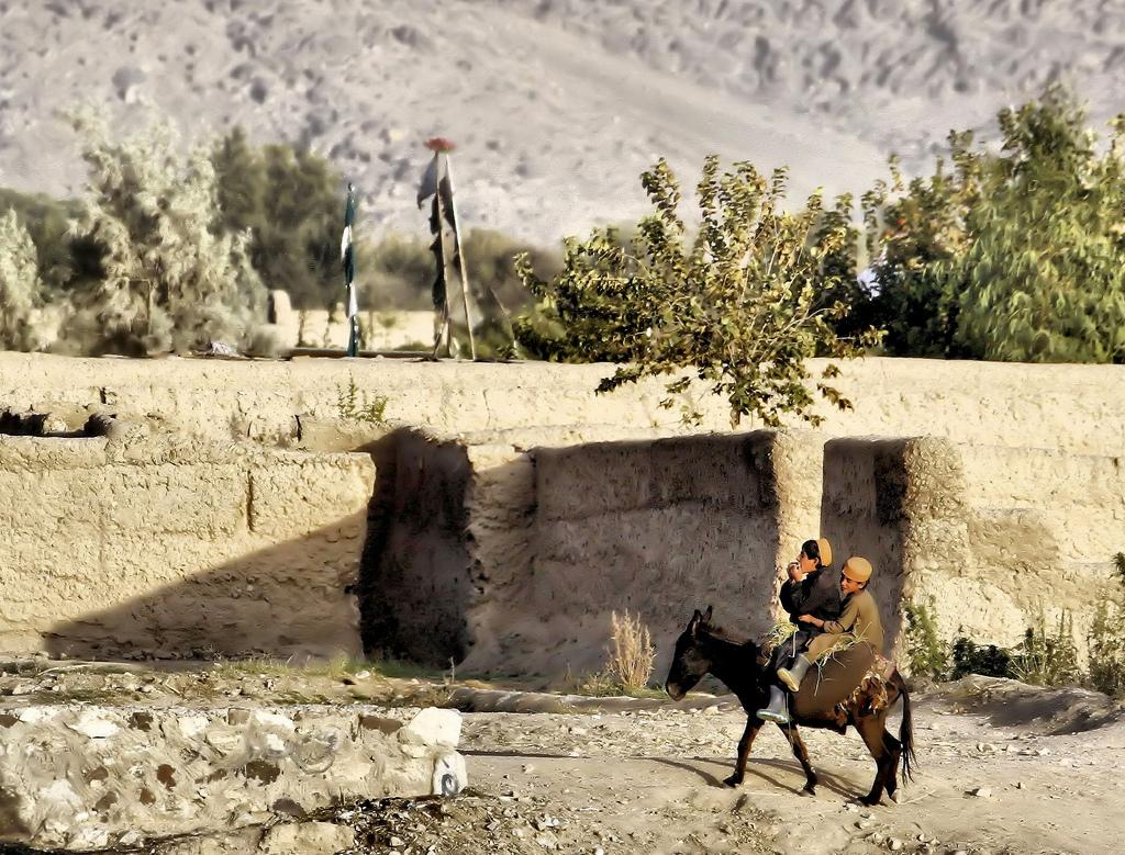 Iraqi Kurds ride a donkey in Iraqi Kurdistan
