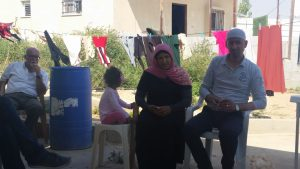 Our host and his wife discuss their situation in Umm al Hiran. Their daughter sits close by.