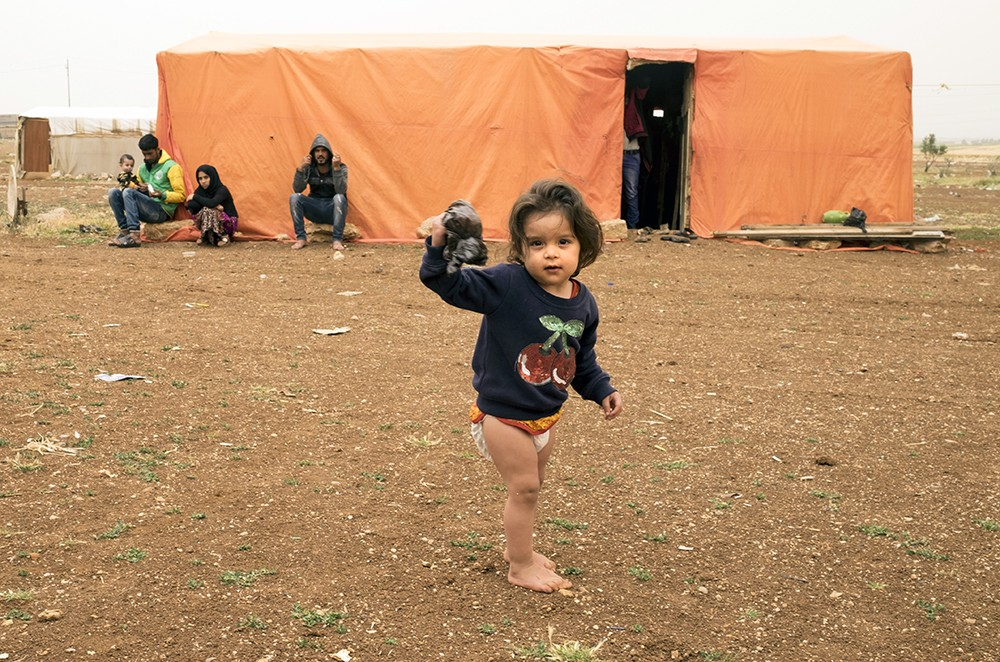 A Bani Murra toddler holds up a trash bag outside the family tent inside a makeshift shared by Bani Murra and Turkmen in northern Jordan. April 2018.