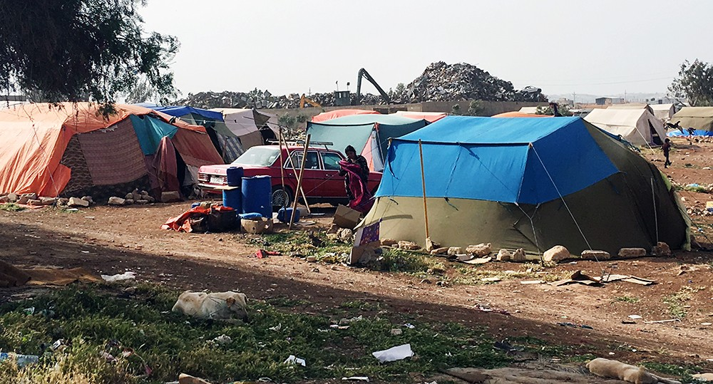 A mountain of trash overlooks a shanty camp in northern Jordan, where Bani Murra and Turkmen minority communities reside.