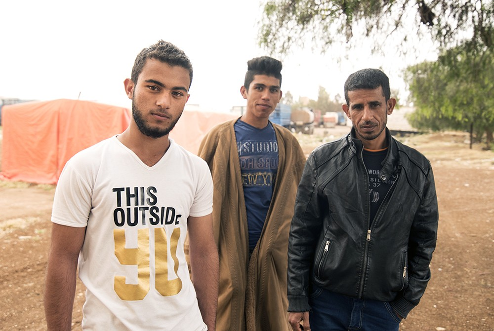 Syrian Bani Murra men pose for a portrait outside a shanty camp