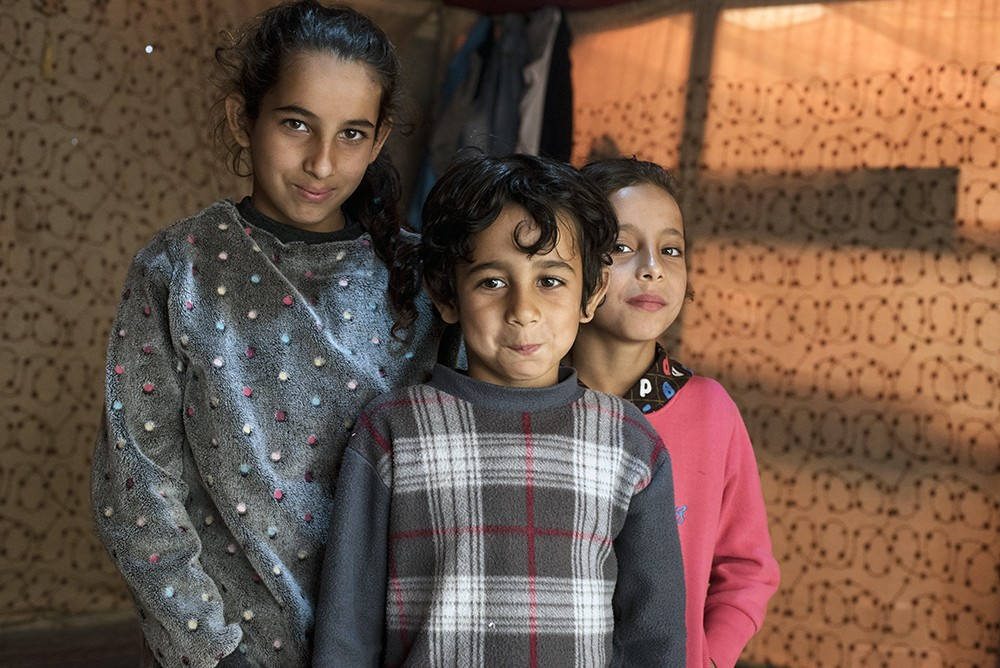Three of Alaa and Awadif Mursalli's five children pose for a portrait