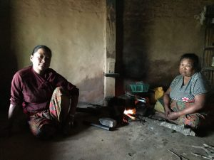 Two indigenous women with disabilities sit on the floor of their house next to a fire in Nepal. They are looking at the camera.
