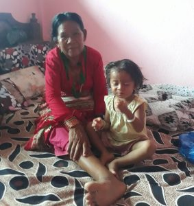 Indigenous woman dressed in red sits on a bed with a young child, in Nepal.