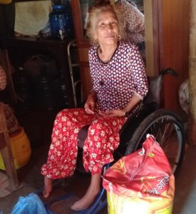 Woman sits in her wheelchair in her house in Nepal, with a bag of rice and other basic supplies that have been received by her during Covid-19 relief programmes.