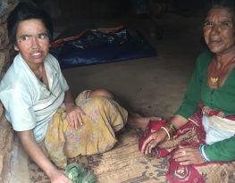 Indigenous women with disabilities sitting facing each other on a mat in their house in rural Nepal.